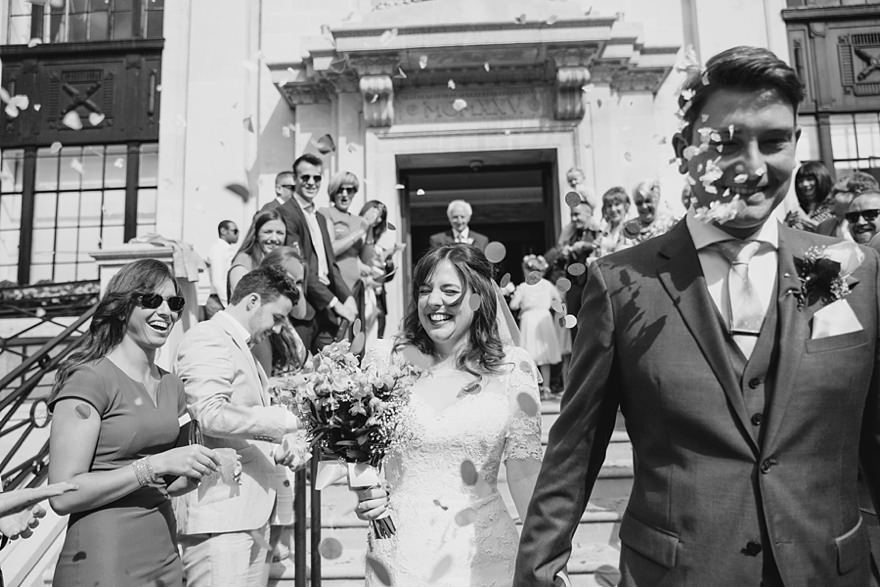 couple walking through a confetti tunnel at their Islington Town Hall London wedding