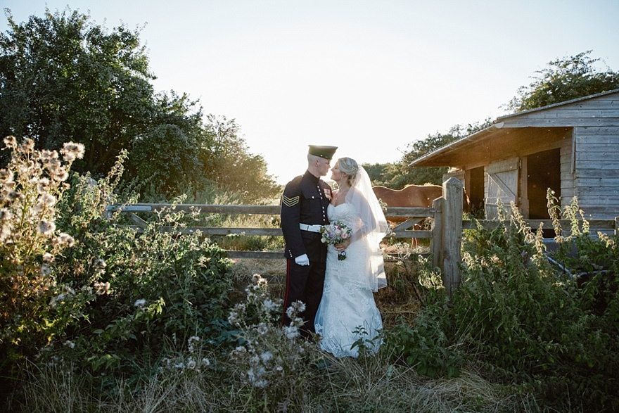 Bride and groom standing outside in golden light, on their wedding day at Milling Barn in Hertfordshire