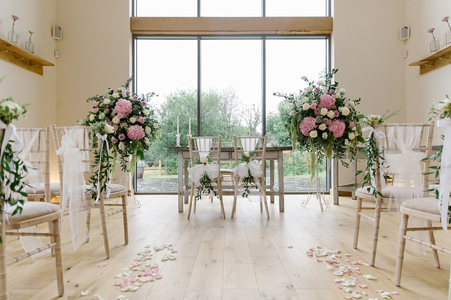 ceremony room set up with pink flowers for a Millbridge Court wedding