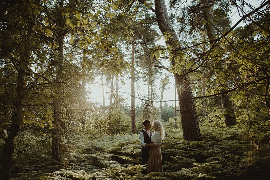 Bedfordshire wedding photographer. Couple standing together under fir trees for their Harlestone Firs engagement photoshoot in Northampton