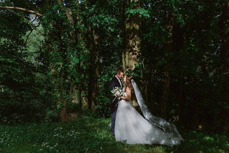 Couple standing together under trees at their Notley Abbey wedding