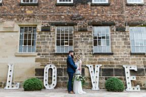 Couple standing together under LOVE signs at the West Mill wedding venue